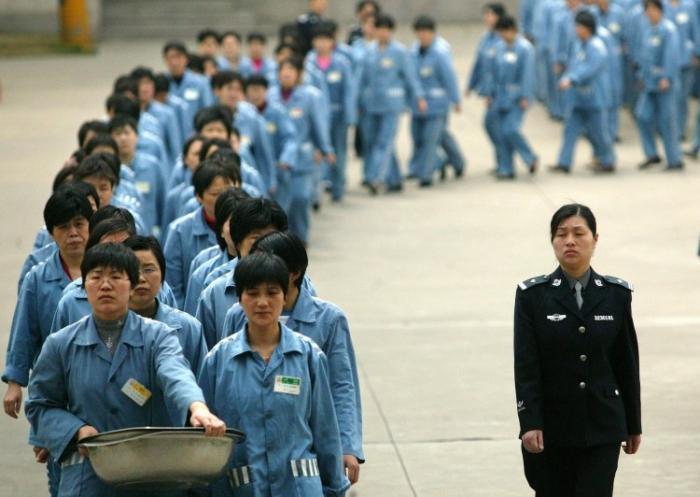 Заключённые идут строем в сопровождении полиции в день открытых дверей в тюрьме в Нанкине, Китай