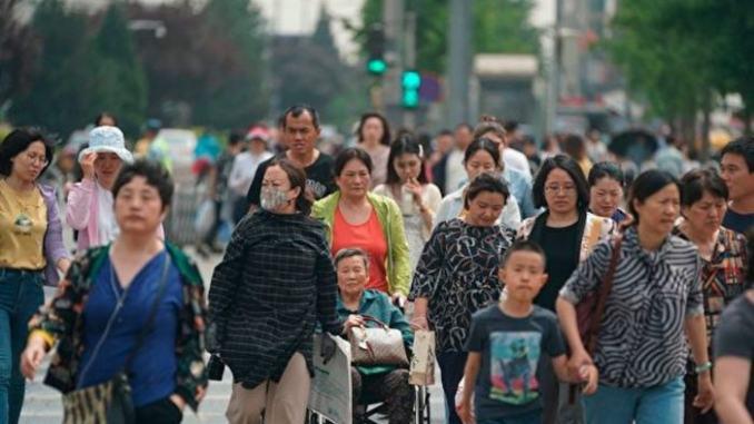 Люди переходят улицу в Пекине
