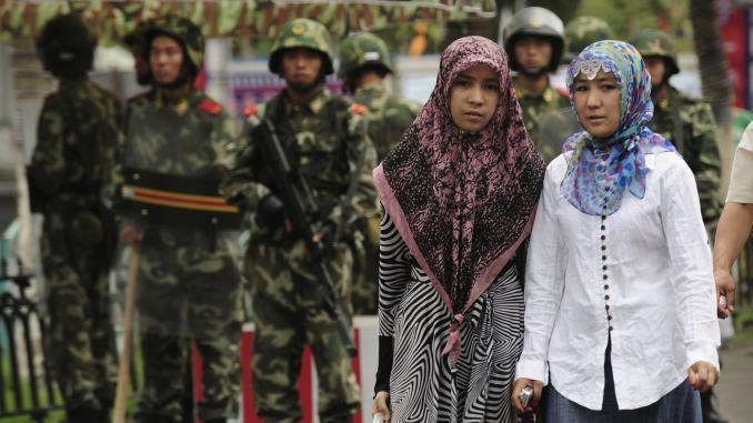 Две уйгурские женщины идут мимо китайских военизированных полицейских, город Урумчи, Синьцзян, Китай