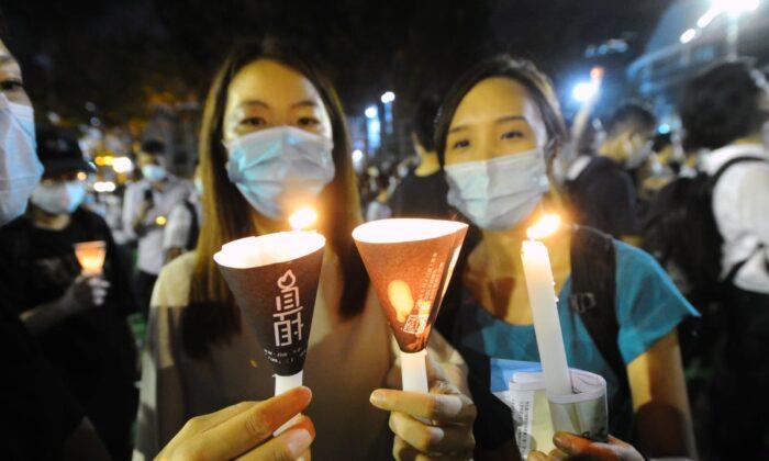 Две девушки держат свечи во время траурной акции в парке Виктория, Гонконг