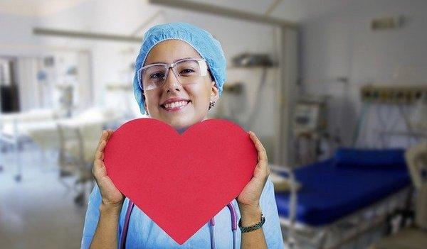 Улыбающаяся женщина-врач с нарисованным сердцем в руках