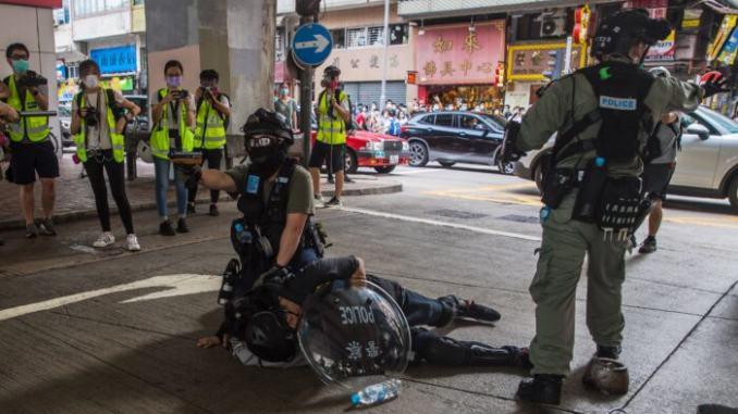 ОМОН задерживает мужчину во время разгона протестующих, участвующих в митинге против нового закона о национальной безопасности в Гонконге