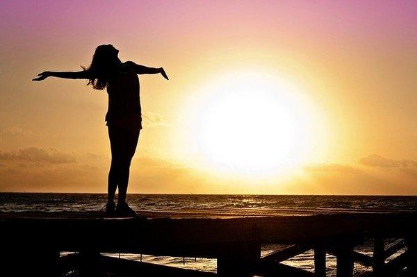 Силуэт женщины с поднятыми руками на фоне восходящего солнца