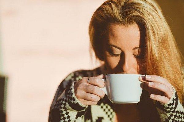 Девушка держит чашку двумя руками