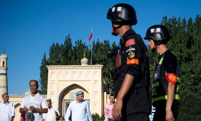 Полиция патрулирует улицы, пока мусульмане покидают мечеть Ид Ках после утренней молитвы в праздник Курбан-байрам в Кашгаре, Синьцзян, Китай