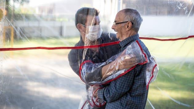 Сын обнимает отца в гериатрической клинике