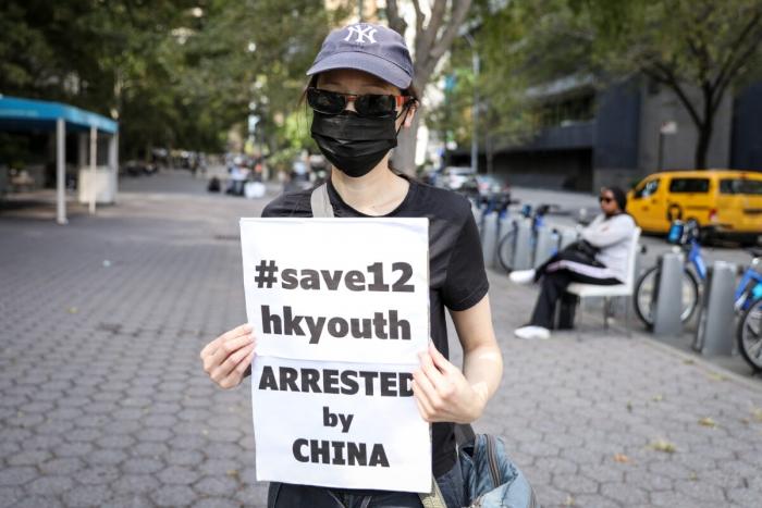 Жительница Гонконга принимает участие в мероприятии перед штаб-квартирой ООН