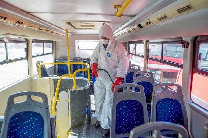 Работник дезинфицирует автобус от нового коронавируса COVID-19, Скопье