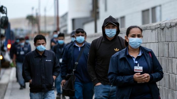 Производственные рабочие в масках идут на завод Hyundai в Тихуане, Мексика