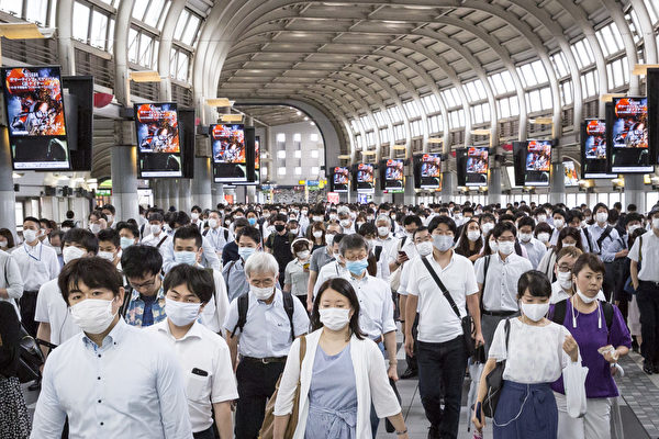Пассажиры в масках проходят через вокзал Синагава в Токио
