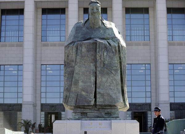 Охранник стоит возле статуи Конфуция у входа в Китайский национальный музей в Пекине