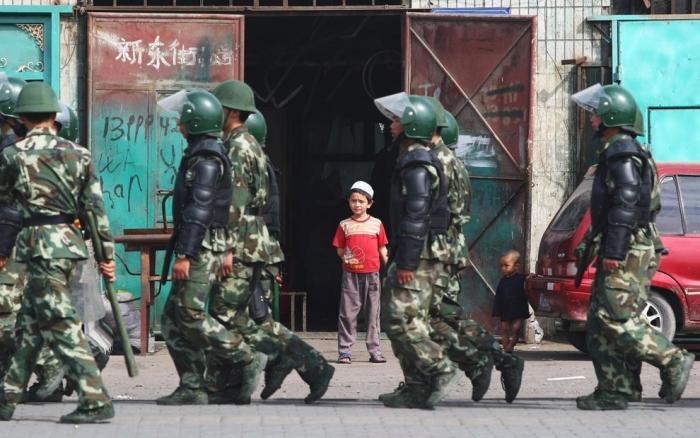 Уйгурские дети наблюдают, как проходят полицейские отряды а Урумчи, Синьцзян, Китай