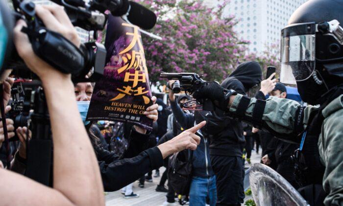 Сотрудник полиции направляет пистолет во время митинга в Гонконге