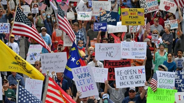Протестующие из общественной организации ReOpen NC требуют, чтобы губернатор Северной Каролины Рой Купер вновь открыл штат Роли, Северная Каролина, 21 апреля 2020 года