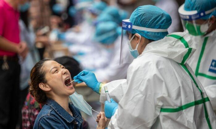 Медицинский работник берёт образец мазка у местного жителя для тестирования на коронавирус в Ухане, Китай