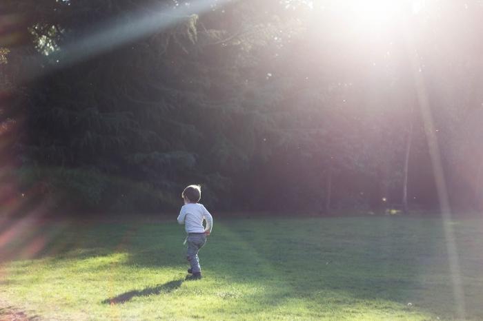 мальчик бежит по траве на лужайке