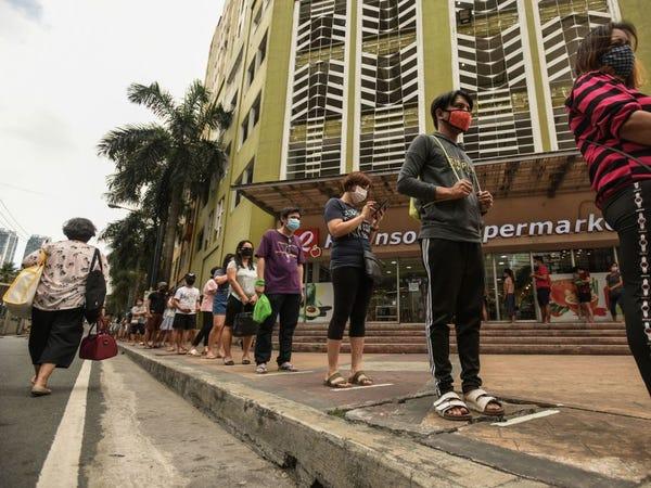 Покупатели держаться на расстоянии в качестве меры социального дистанцирования на фоне опасений по поводу коронавируса COVID-19, стоя в очереди у супермаркета в Маниле, 17 марта 2020 года