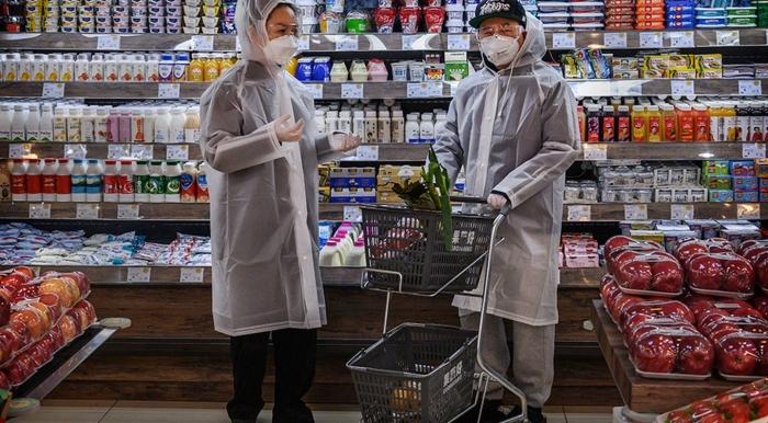 Китайская пара в плащах и защитных масках делает покупки в супермаркете в Пекине