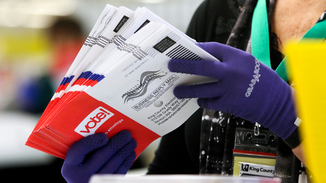 Работник избирательной комиссии сортирует бюллетени для голосования по почте