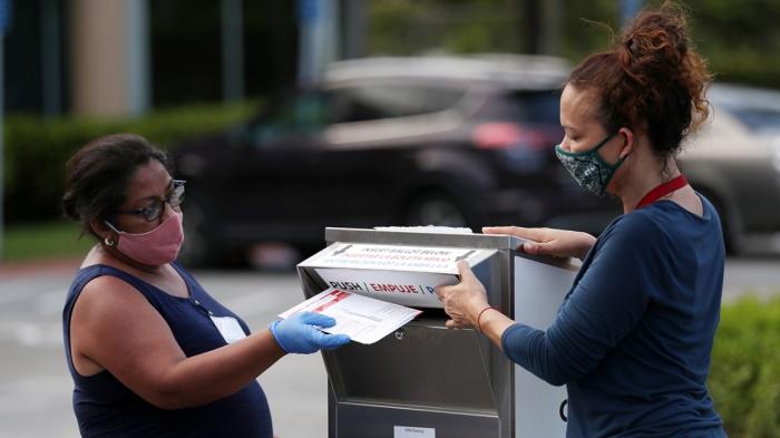 Работники избирательных участков бросают бюллетени в почтовый ящик в день выборов в Дорале, штат Флорида