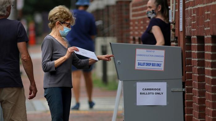 Избиратель опускает бюллетень для голосования по почте в ящик в Кембридже