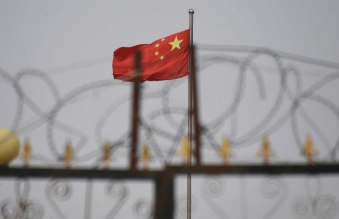 Китайский флаг за колючей проволокой на жилом комплексе в уезде Янгисаре, Синьцзян-Уйгурский автономный район, 4 июня 2019 года