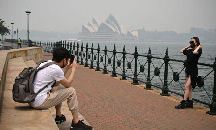 Туристы в масках фотографируются на фоне Оперного театра, окутанного дымом из-за близлежащих лесных пожаров в Сиднее