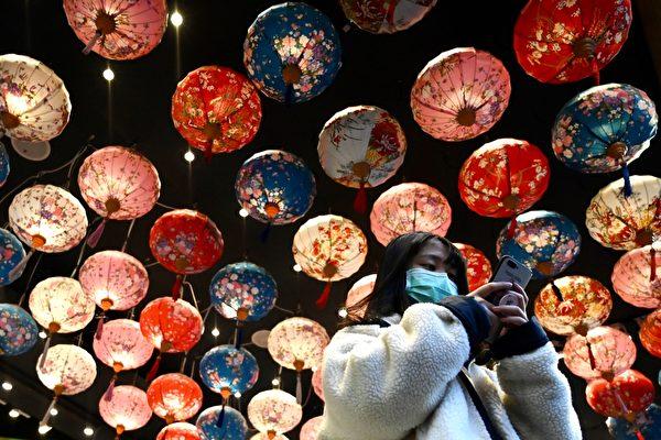 Женщина в защитной маске проходит под фонарями в районе Симэнь в Тайбэе во время Нового года по лунному календарю, 30 января 2020 года