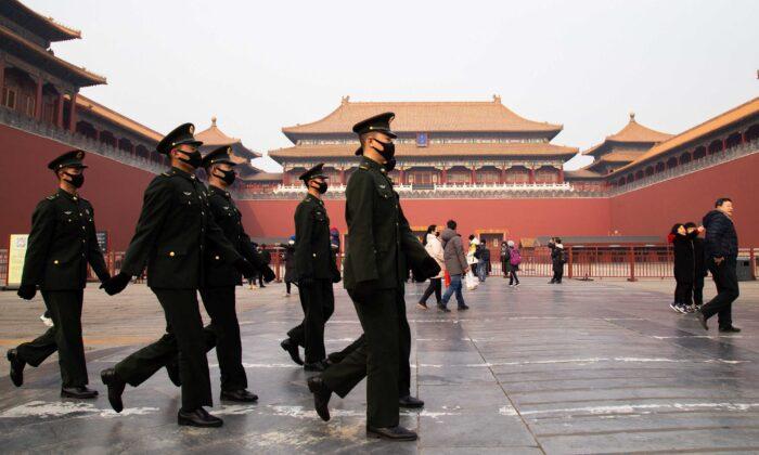 Китайские милиционеры идут мимо закрытого входа в Запретный город в Пекине