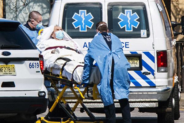 Медицинские работники в масках и средствах индивидуальной защиты (СИЗ) загружают пациента в машину скорой помощи