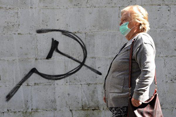 Женщина в маске проходит мимо символа серпа и молота во время ярмарки в городе Карбальино, на северо-западе Испании, 16 мая 2020 года