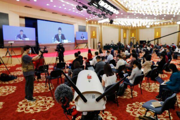 Журналисты на пресс-конференции Го Вэйминя, представителя Национального комитета Народной политической консультативной конференции Китая (НПКСК), который выступает по видеосвязи в медиа-центре в Пекине