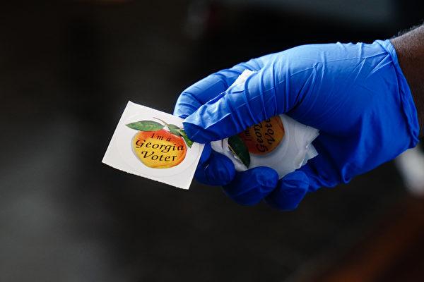 Работник избирательного участка держит наклейку «Я избиратель из Джорджии» и передает избирателю в Атланте, штат Джорджия, 9 июня 2020 года