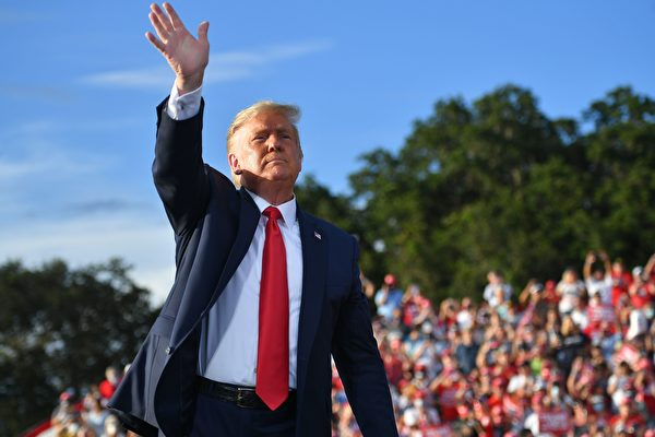 Президент США Дональд Трамп машет рукой во время предвыборного митинга