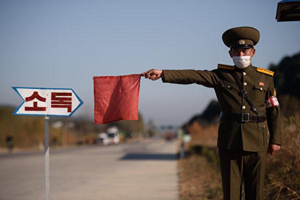 Офицер общественной безопасности красным флажком остановливает такси для дезинфекции в рамках профилактических мер против коронавируса COVID-19 на дороге у въезда в Вонсан, провинция Канвондо, 29 октября 2020 года