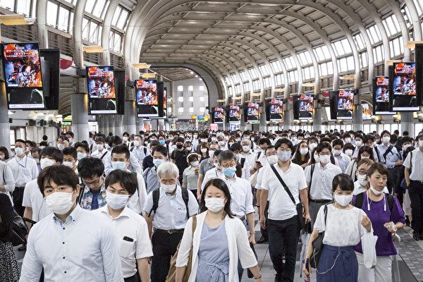 Пассажиры в масках проходят через вокзал Синагава, Токио, Япония, 10 июля 2020 года