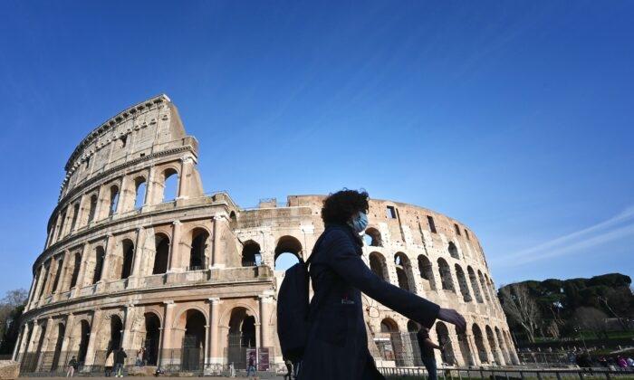 Турист в маске из-за мер предосторожности против распространения нового коронавируса COVID-19 проходит мимо закрытого Колизея в Риме 10 марта 2020 года