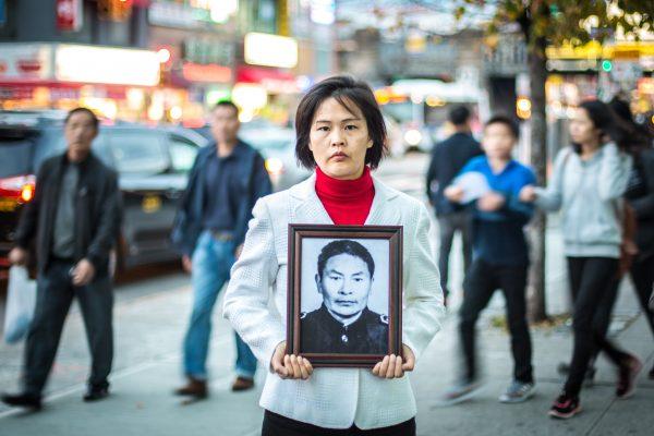 Цзян Ли держит фотографию отца. район Флашинг в Куинсе, штат Нью-Йорк, 1 ноября 2015 года