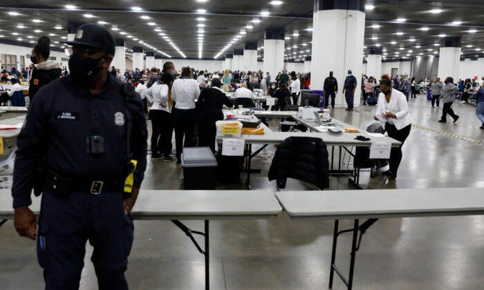 Офицер полиции Детройта стоит на страже, пока сотрудники избирательных комиссий работают над подсчетом бюллетений для заочного голосования на всеобщих выборах 2020 года, Детройт, штат Мичиган, 4 ноября 2020 года