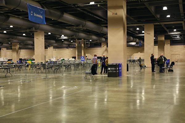 В комнате для подсчета голосов в конференц-центре Филадельфии наблюдатели за выборами стоят за барьерами вдали от места подсчета голосов, штат Пенсильвания, 6 ноября 2020 года