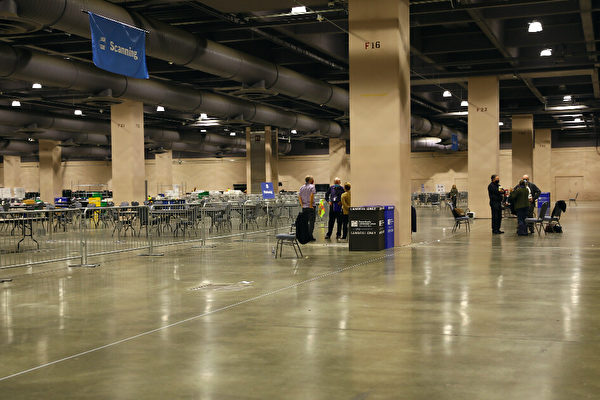 В комнате для подсчета голосов в конференц-центре Филадельфии наблюдатели за выборами стоят за барьерами вдали от места подсчета голосов. Штат Пенсильвания, 6 ноября 2020 года