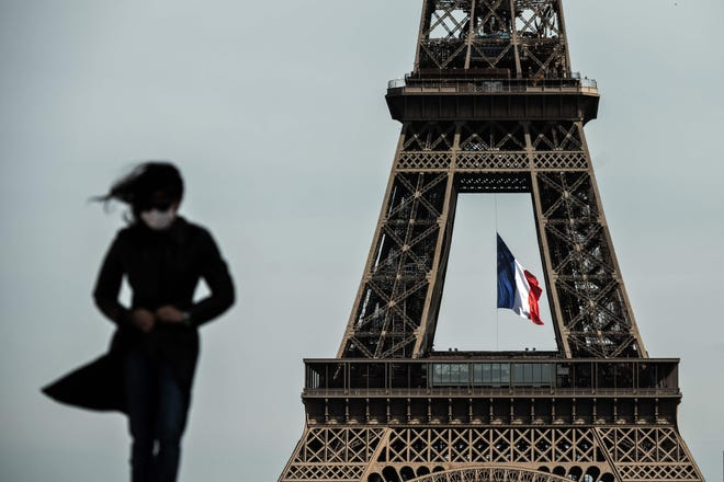 Женщина в маске идёт, пока национальный флаг Франции развевается на Эйфелевой башне на заднем плане в Париже, 11 мая 2020 года