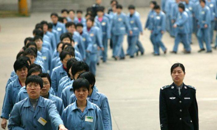 Заключенные идут рядом с охранником в тюрьме в Нанкине