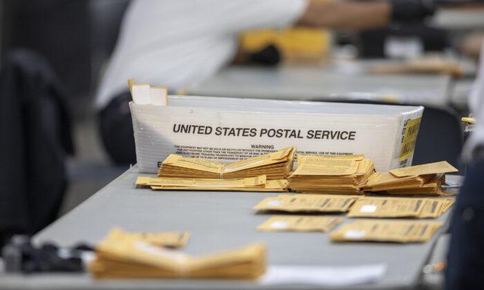 Бюллетени для досрочного голосования лежат на столе в ожидании обработки в Кобо-центре, Детройт, штат Мичиган, 4 ноября 2020 год