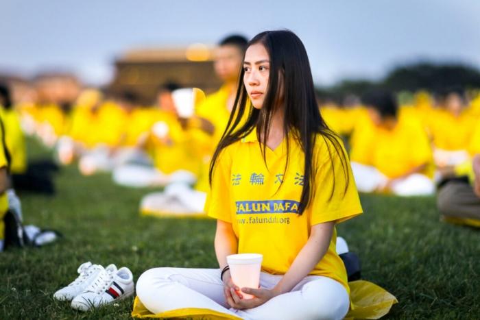 Практикующие Фалуньгун участвуют в бдении при свечах в 20-ю головщину преследования Фалуньгун в Китае на лужайке Капитолийского холма, 18 июля 2019 года