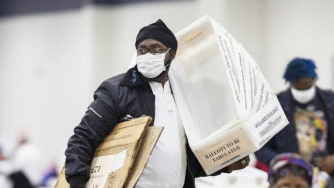 Сотрудник Департамента выборов Детройта несет пустые ящики для бюллетеней, после того, как почти завершился подсчёт бюллетеней, отправленных по почте в Детройте, штат Мичиган, 4 ноября 2020 года