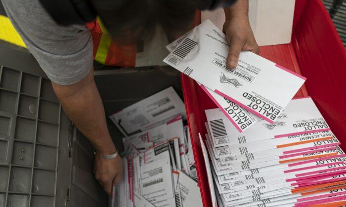 Работник избирательной комиссии сортирует бюллетени в округе Малтнома, Портленд, штат Орегон, 2 ноября 2020 года