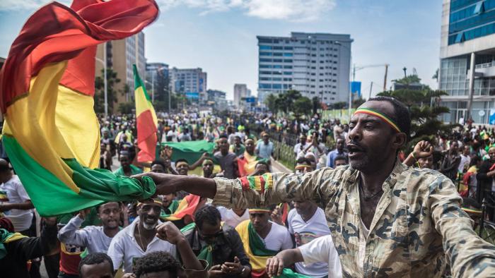 Эфиопы размахивают национальными флагами и празднуют на улицах Аддис-Абебы 9 сентября 2018 года, когда Берхану Нега вернулся после 11 лет в изгнании