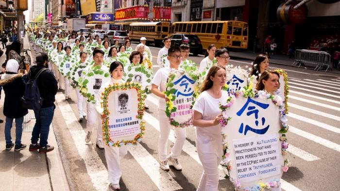 Практикующие Фалуньгун держат венки с фотографиями людей, убитых в Китае за свои убеждения. Тысячи практикующих Фалуньгун со всего мира маршируют на параде по 42-й улице в Нью-Йорке в честь Всемирного дня Фалунь Дафа 12 мая 2017 годае в честь Всемирного дня Фалунь Дафа 12 мая 2017 года