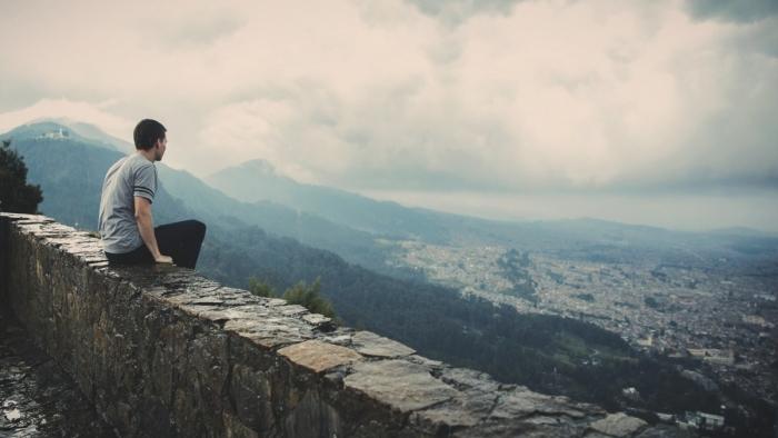 мужчина на каменной ограде